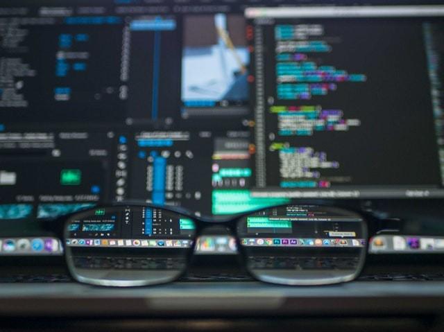 Alteryx Aktie investieren - Eine Brille im Vordergrund und große Datenmengen auf Bildschirmen im Hintergrund