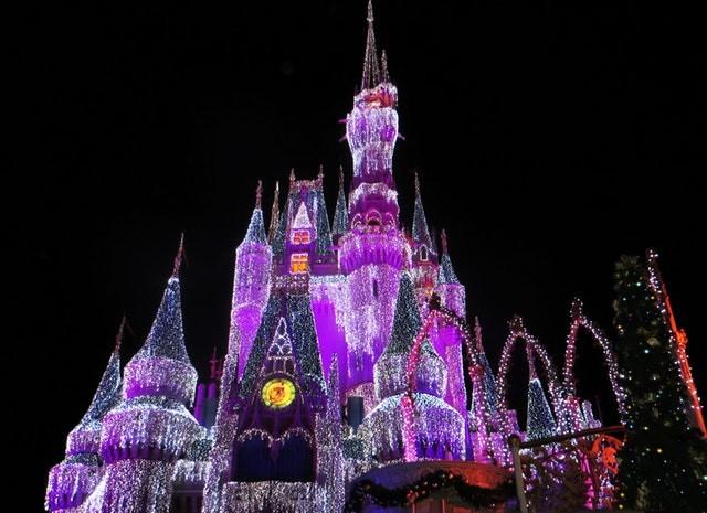 Disney Aktie investieren - Ein Märchenschloss in der Nacht mit bunter Beleuchtung
