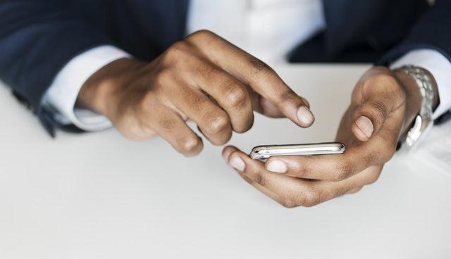 Tencent Aktie - Mobiles bezahlen Ausschnitt einer Person mit Handy in der Hand