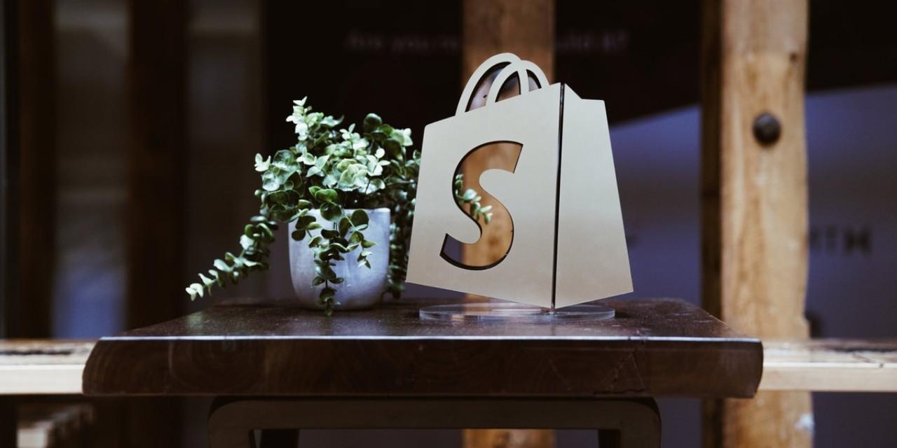 Shopify Aktie News - Shopify Logo auf einem Tisch neben einer Pflanze - Beitragsbild