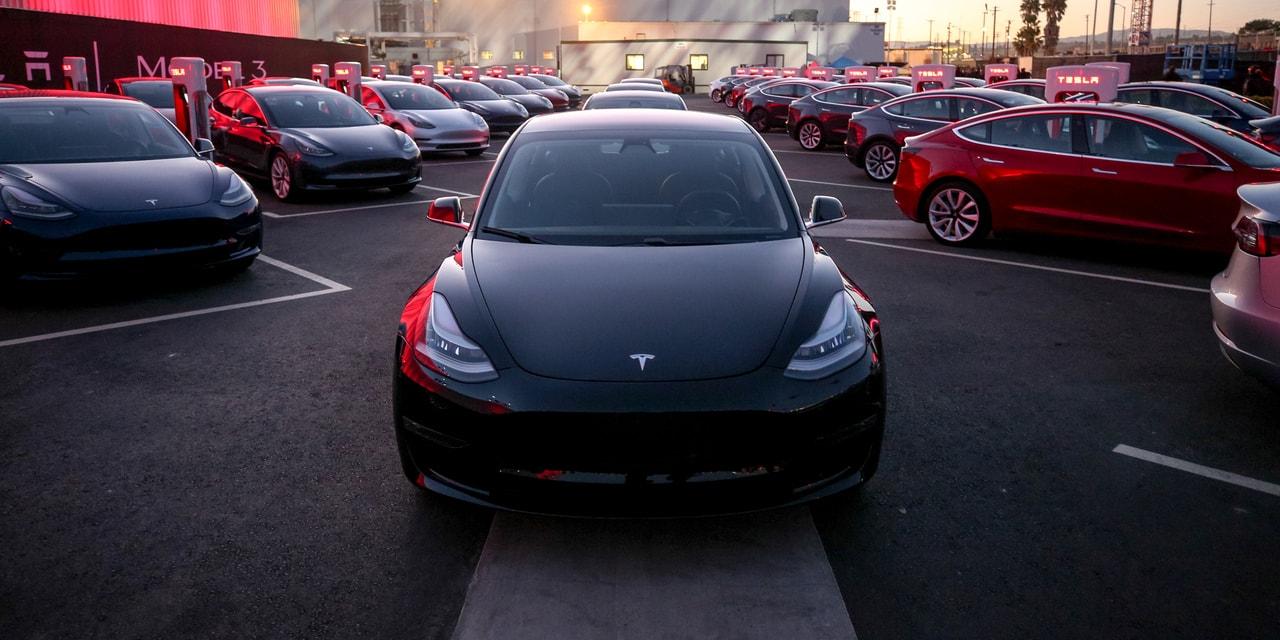 Tesla Aktie investieren - Viele Modelle des Tesla Model 3 auf einem Parkplatz