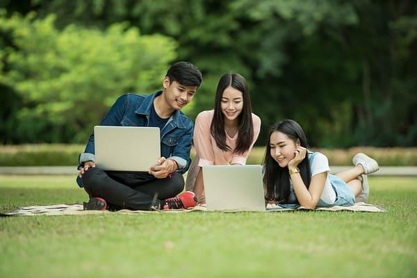 Baidu Aktie - Videostreaming mit iQIYI - 3 Studenten auf der Wiese mit Laptop
