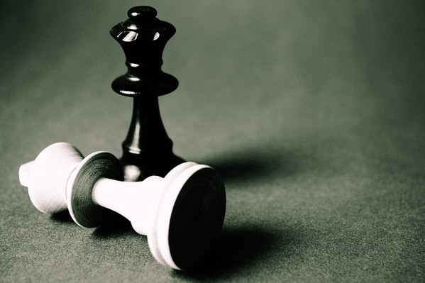 In Digitalisierung investieren - Eine weiße Schachfigur liegt und daneben steht eine schwarze Schachfigur