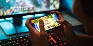 Tencent Aktie - Steigende Nutzerzahlen trotz Coronavirus - Person spielt Videospiel auf Handy und im Hintergrund leuchtende Tastatur und Bildschirm