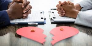 Match Group Aktie - Zerrissenes Herz auf Schreibtisch mit zwei gegenüber-sitzenden Personen