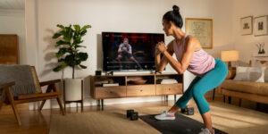 Peloton Aktie - Hype - Frau trainiert zu Hause vor TV