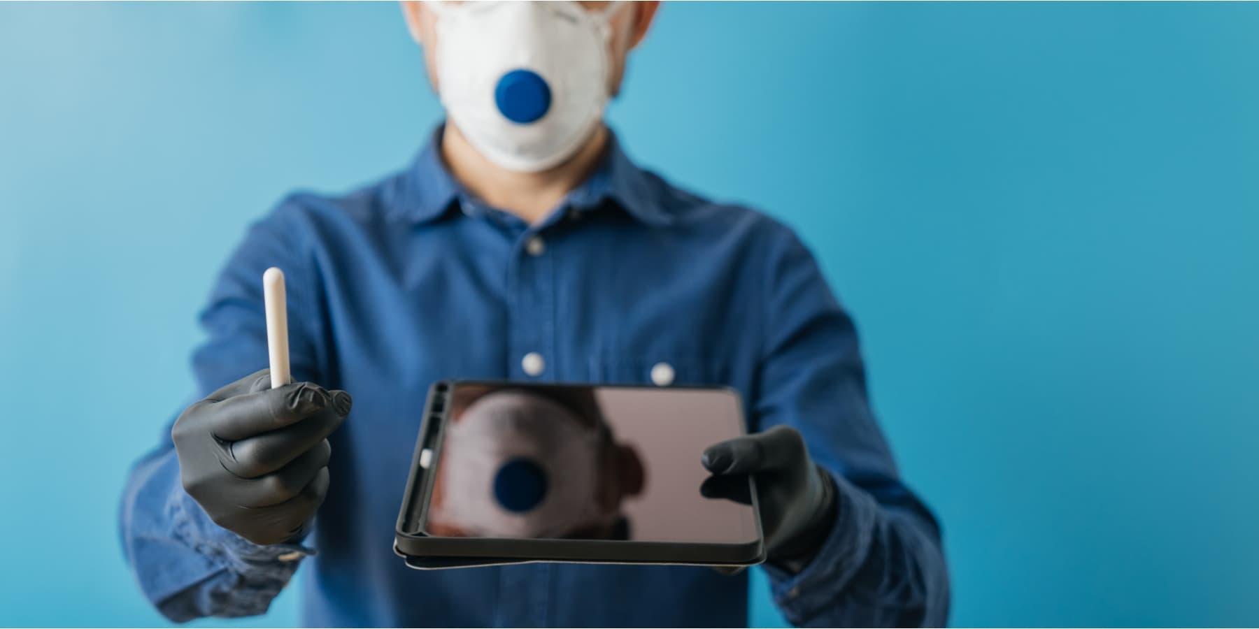 DocuSign Aktie Corona Rausch - Mann mit Mundschutz und Handschuhen hält iPad und Stift zur digitalen Unterschrift