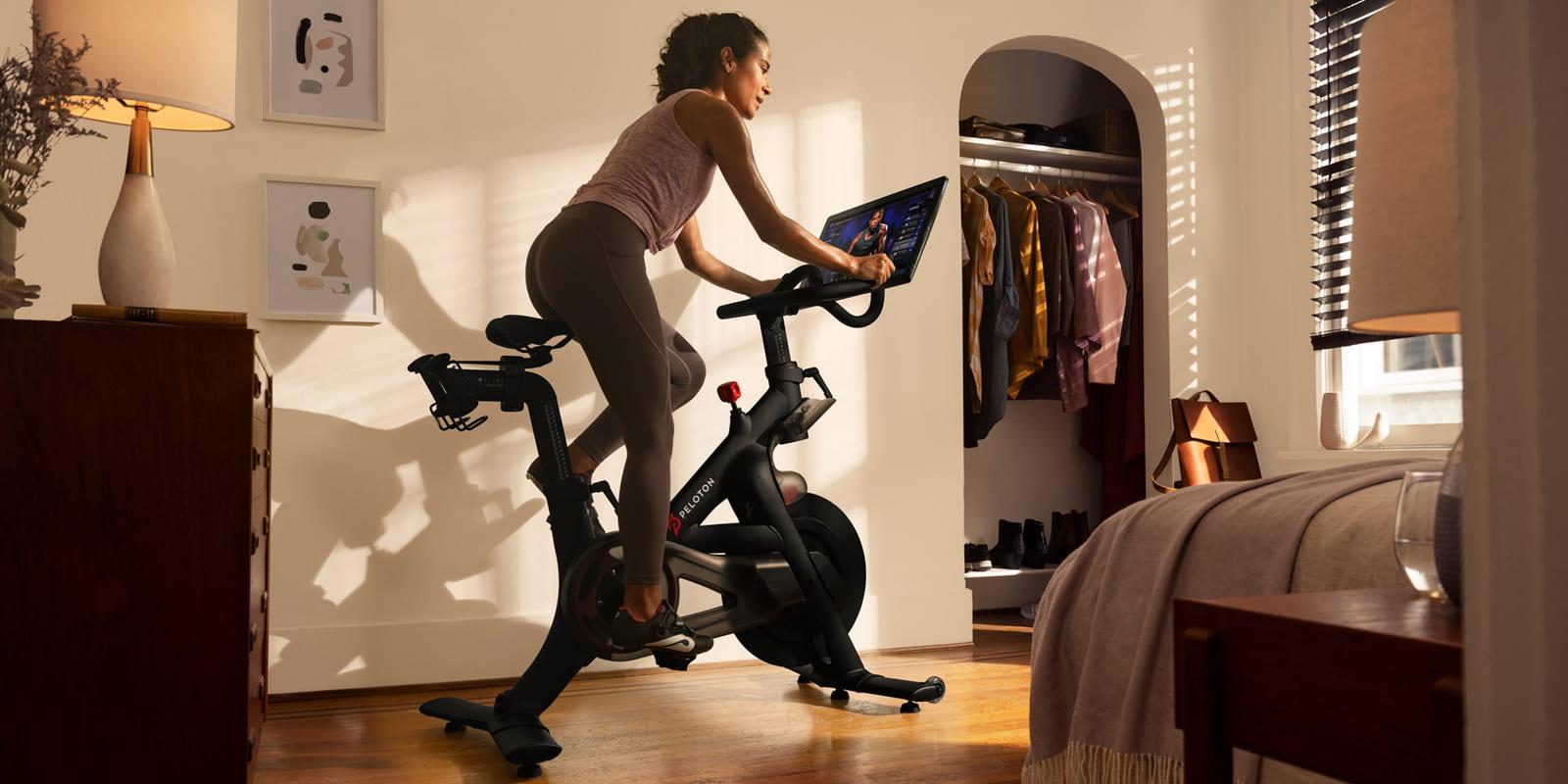Peloton Kulturphaenomen - Frau auf Spinning Rad mit Bildschirm in Wohnung