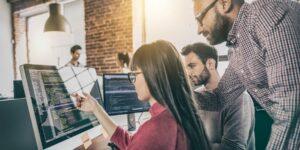 Pluralsight Cloud Aktie - Kollegen vor Bildschirm mit Code diskutieren